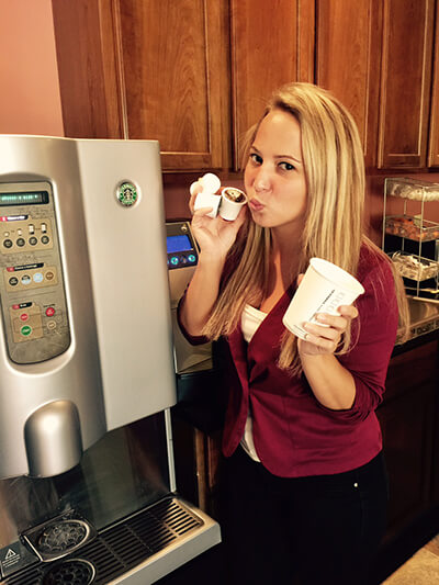 Malley holding k cups in front of the coffee maker
